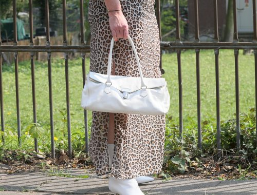 A long leopard print skirt with white boots and white handbag